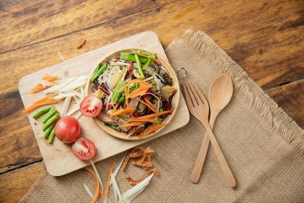 ソムタムタイ、木製の背景にタイのパパイヤサラダ 無料写真