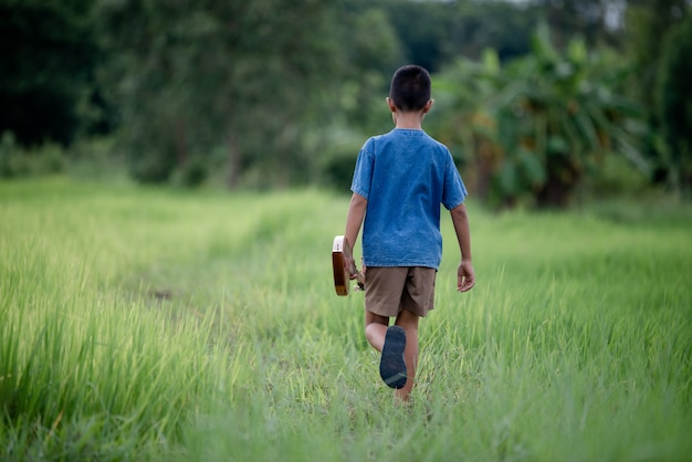アウトドア、生活国で手作りのギターを持つアジアの少年 無料写真