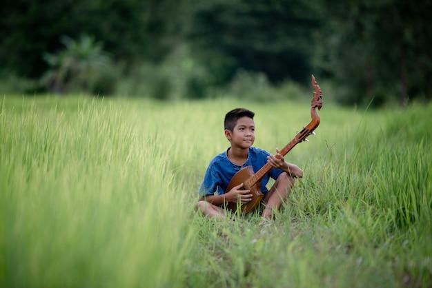 Азиатский мальчик с гитарой ручной работы на природе Бесплатные Фотографии