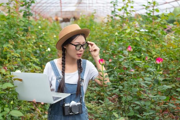 Аграрная женщина держа таблетку в розарии. Бесплатные Фотографии