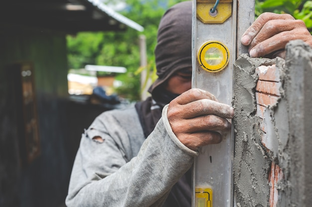 レンガ造り。建設労働者がレンガの壁を構築します。 無料写真