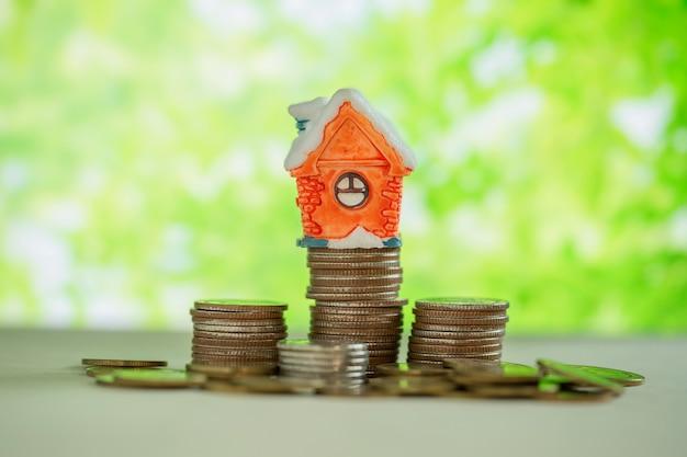 緑のぼかしとコインのスタック上のミニハウス。 無料写真