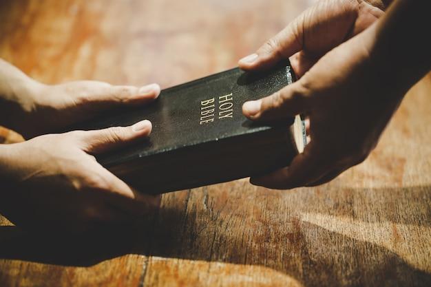 礼拝を祈って手を繋いでいる人々のグループ 無料写真