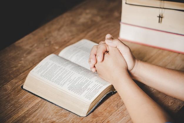 精神性と宗教、信仰のための教会概念の聖書に祈りで折り畳まれた手。 無料写真