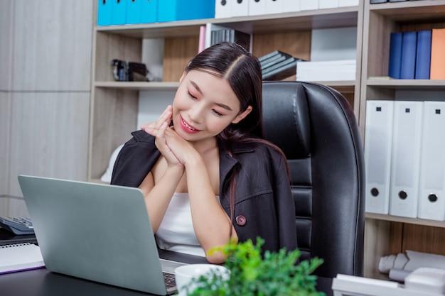 Коммерсантка работая в офисе с улыбкой пока сидящ. Бесплатные Фотографии