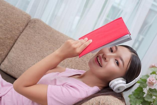 音楽を聴くと本を読むソファに横たわった少女。 無料写真