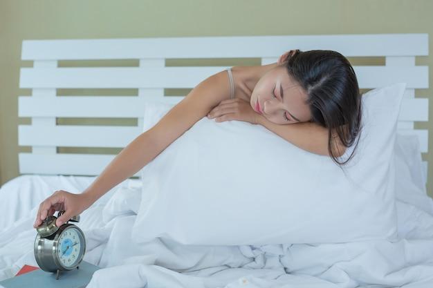 美しい若い女性が寝ており、自宅の寝室に目覚まし時計があります。 無料写真