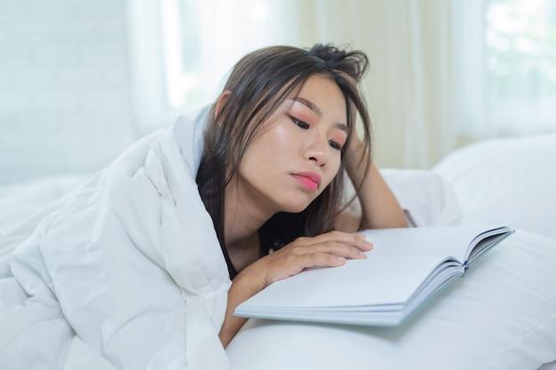 音楽を聞きながら本を読んでベッドに横たわっている少女。 無料写真