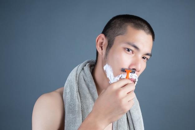 灰色の顔を剃るハンサムな男を剃る 無料写真
