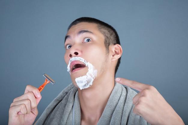 Красивый бритый парень побрился на лицо на сером Бесплатные Фотографии