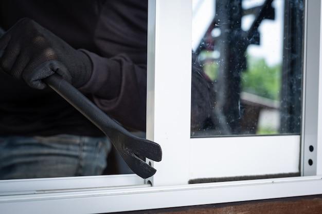 泥棒は黒い帽子を着用し、窓をこじ開け、物を盗みます。 無料写真