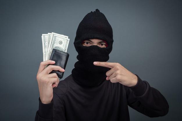 Вор носит черную шляпу с украденным кошельком на сером Бесплатные Фотографии
