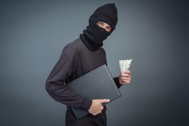 泥棒は、パスワードハッキング活動のためにラップトップコンピューターを使用してクレジットカードを保持しています。 無料写真