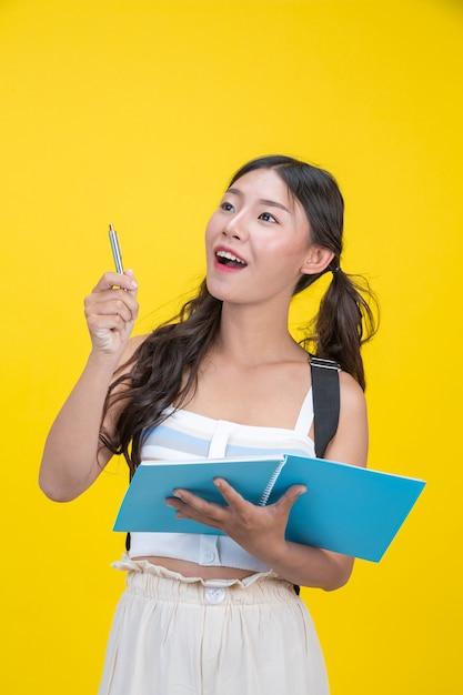 Красивые студентки держат блокноты и ручки Бесплатные Фотографии