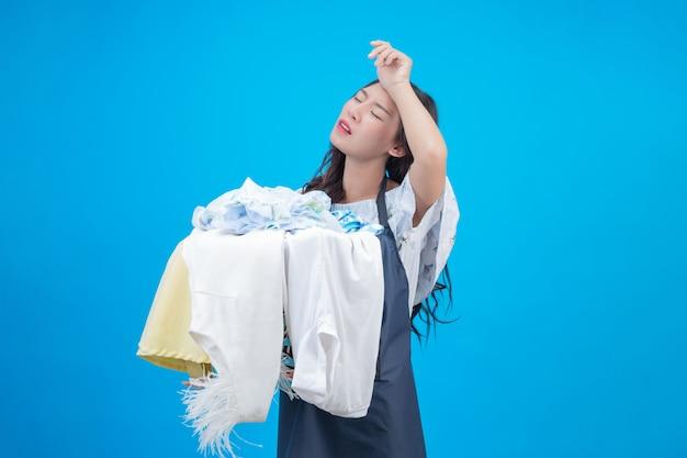 Красивая женщина, держащая ткань, подготовленную для стирки на синем Бесплатные Фотографии