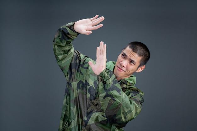 若い男はカモフラージュのレインコートを着ており、さまざまなジェスチャーを示しています。 無料写真