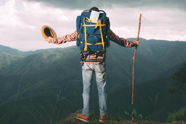 男性は、森のバックパックで熱帯林の山を見るために立ちます。冒険、旅行、登山。 無料写真