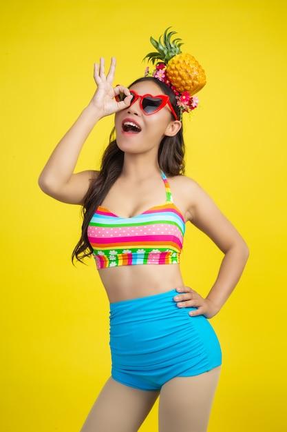 黄色のパイナップルポーズを保持している水着で美しい女性 無料写真
