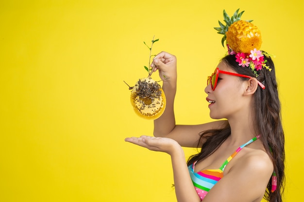 黄色のハニカムポーズを運ぶ水着で美しい女性 無料写真