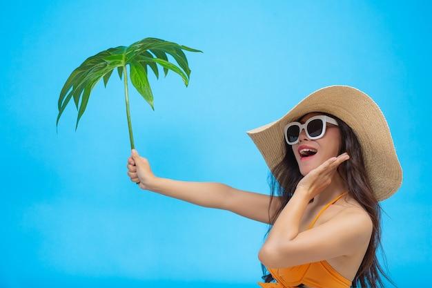 Красивая женщина в купальнике держит зеленый лист позирует на синем Бесплатные Фотографии