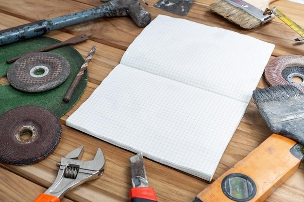 ホワイトペーパーと木製の床に手動ツールを設定します。 無料写真