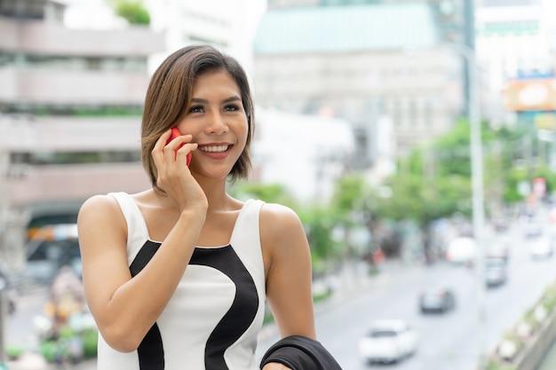 モダンな建物で、スマートフォンと話している幸福な若いきれいな女性 無料写真