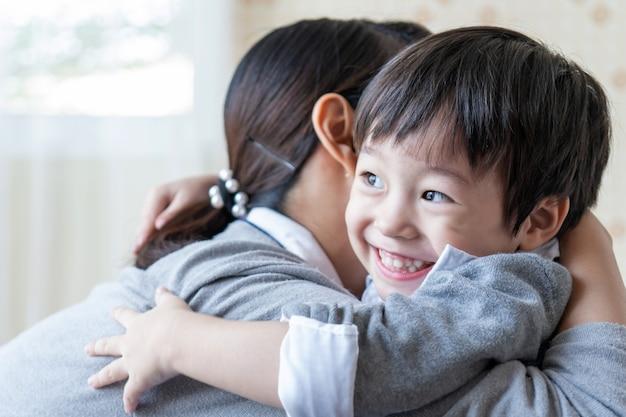 幸せそうに笑って、自宅で家族の概念と母親を抱いてアジアのかわいい男の子 無料写真