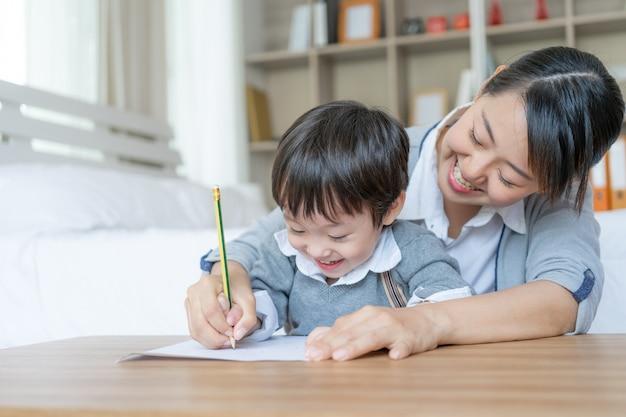 若い母親は、はしごに鉛筆を持っている息子の手を捕まえ、自宅の就学前の白い紙に書き留めました 無料写真