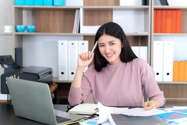 ライフスタイルオフィスの机の上のラップトップコンピューターを使用して美しいアジアビジネス若い女性 無料写真