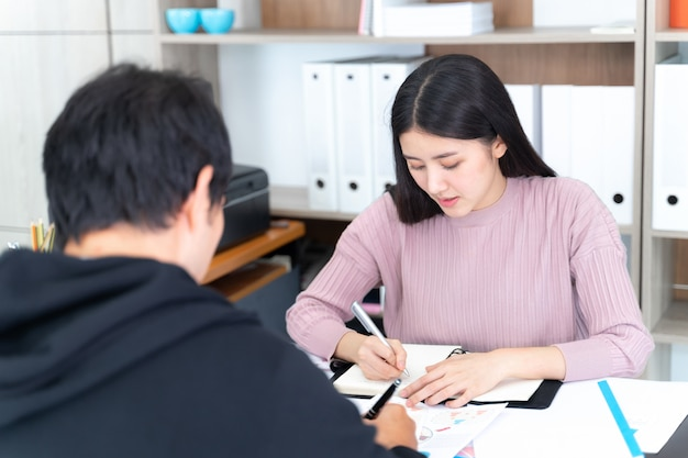 働く女性は、オフィスで若い男との会議を持っています 無料写真