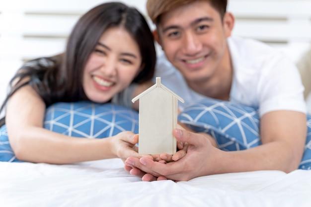 Молодая пара держит игрушку дома на кровати Бесплатные Фотографии