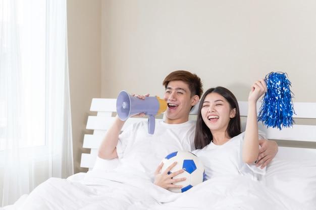 Молодой азиатский красивый муж и красивая жена очень радуются за свою команду Бесплатные Фотографии