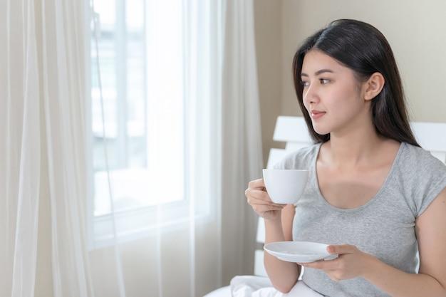 Азиатская красивая женщина, сидя на кровати в спальне и держа чашку кофе в руке Бесплатные Фотографии