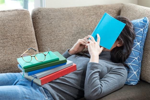 書籍のスタックが彼女の体に置かれている間ソファで寝ているアジアの若い女性 無料写真