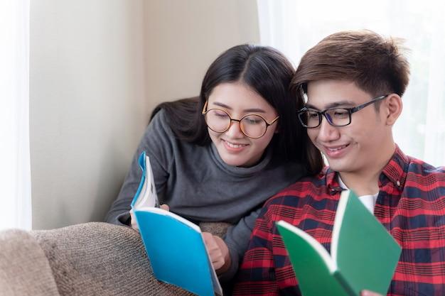 ソファに座って本を読んで愛する若いカップル 無料写真