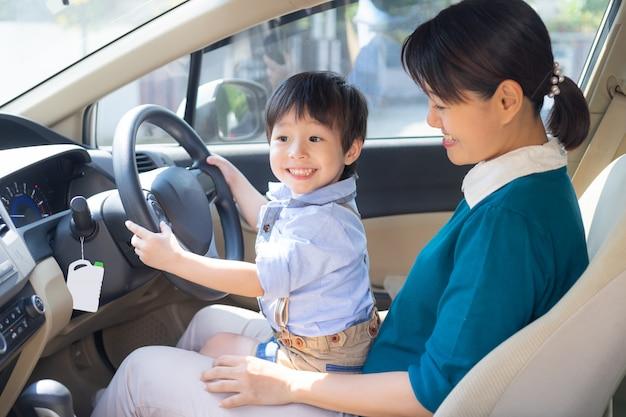 母と息子は車のステアリングホイールで遊ぶことを楽しむ 無料写真