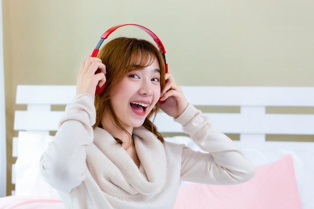 女の子はヘッドフォンを着てベッドで音楽を楽しんでいた 無料写真