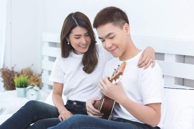 Счастливая азиатская пара на кровати у себя дома Бесплатные Фотографии