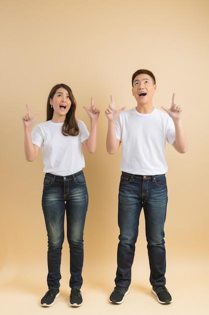 Молодая счастливая азиатская пара представляя символы дома Бесплатные Фотографии