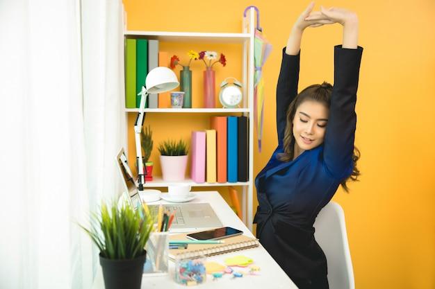 Веселый бизнес-леди работает на ноутбуке в офисе Бесплатные Фотографии