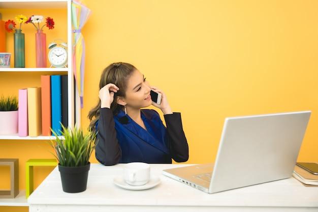 オフィスでラップトップに取り組んでいる陽気なビジネス女性 無料写真