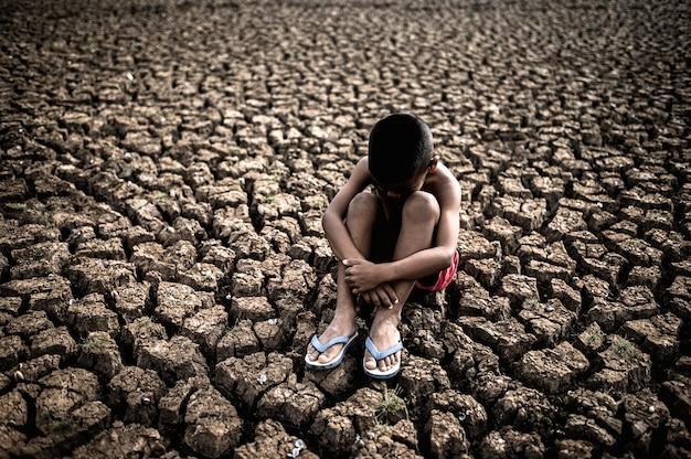 膝を抱いて座っている男性、曲がった、乾燥した土壌で曲がった、地球温暖化 無料写真