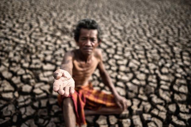 Пожилой мужчина сидел, прося дождя в сухой сезон, глобального потепления Бесплатные Фотографии