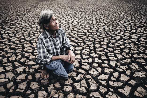 高齢者の女性が座って、乾燥した天候、地球温暖化の空を見ています 無料写真