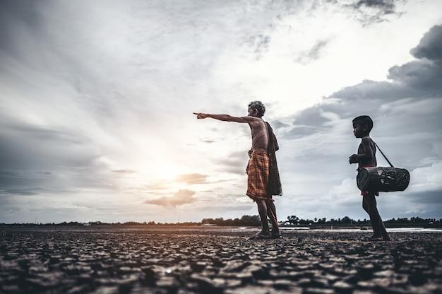 Пожилые мужчины и мальчик находят рыбу на сухой земле, глобальное потепление Бесплатные Фотографии