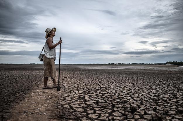 乾燥した土壌と漁具の上に立っている女性、地球温暖化と水危機 無料写真