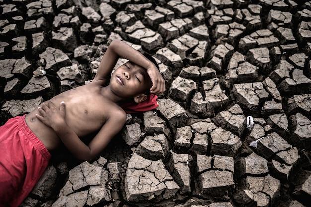 少年は平らに横たわり、乾いた土の上に腹と額に手を置いた。 無料写真