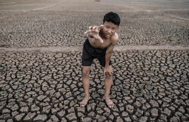 少年はひざをかがめて立ち、雨、地球温暖化、水危機を訴える印をつけました。 無料写真