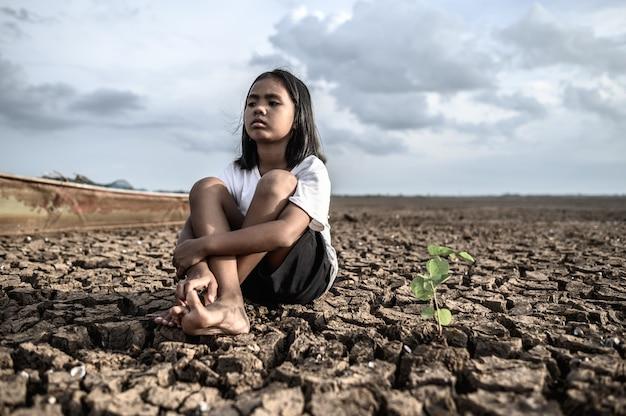 Девочки сидят, обнимая колени, глядя на небо и имея деревья на сухой земле Бесплатные Фотографии