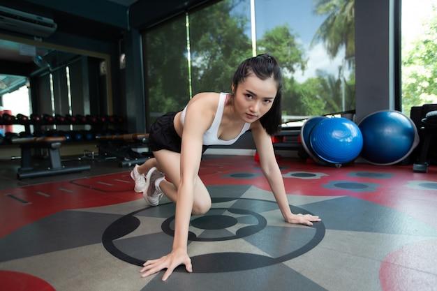 若い女性は、運動する前に床を押してジムで膝を曲げてウォームアップします。 無料写真